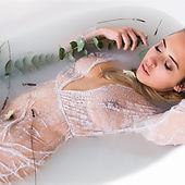 woman lying in milk bath in a white lace dress with eucalyptus