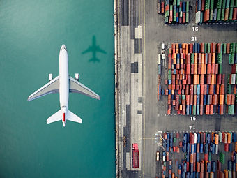 airplane-flying-over-container-port-6360