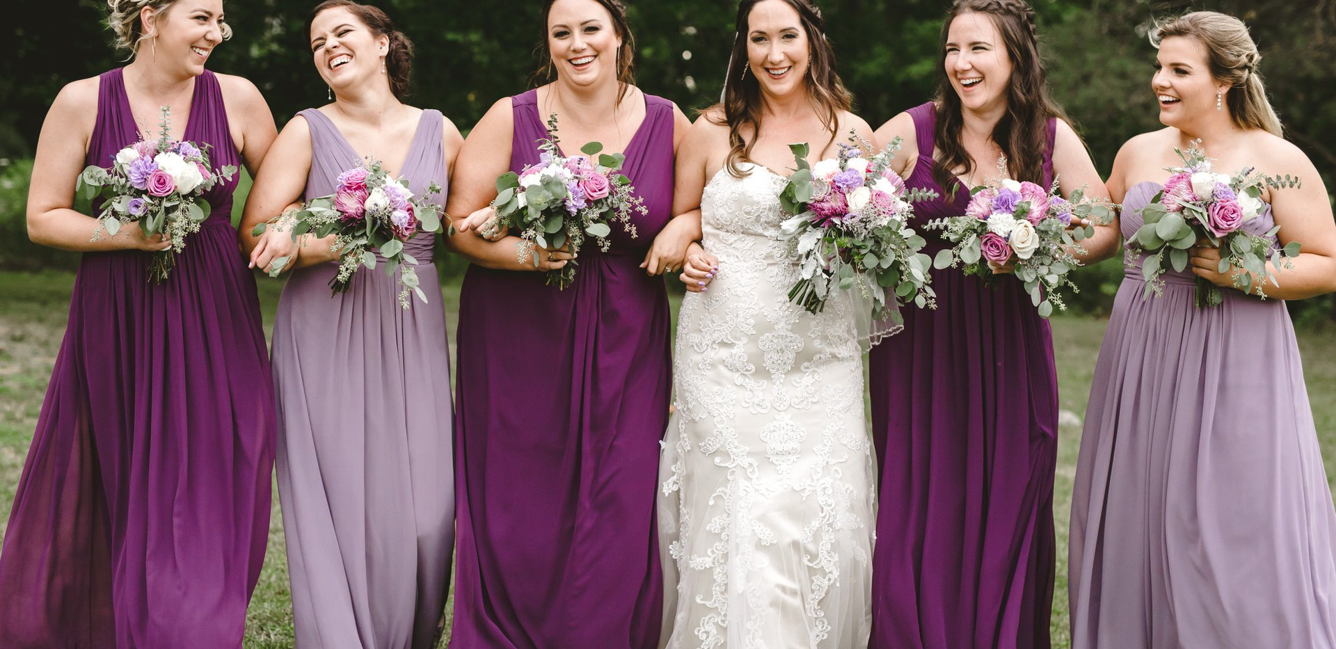 Bridal Party walking with linked arms and bouquets (wearing lavender and merlot mis-matched bridesmaid dresses)