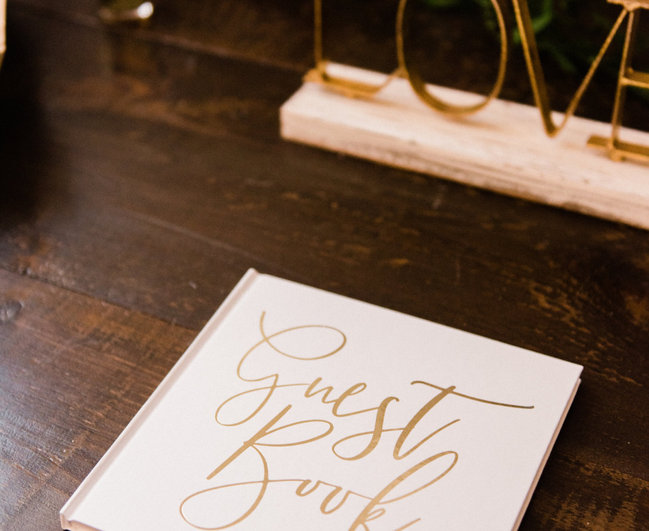 close up of elegant white and gold guest book and decor accessories on guest book, gifts and cards table