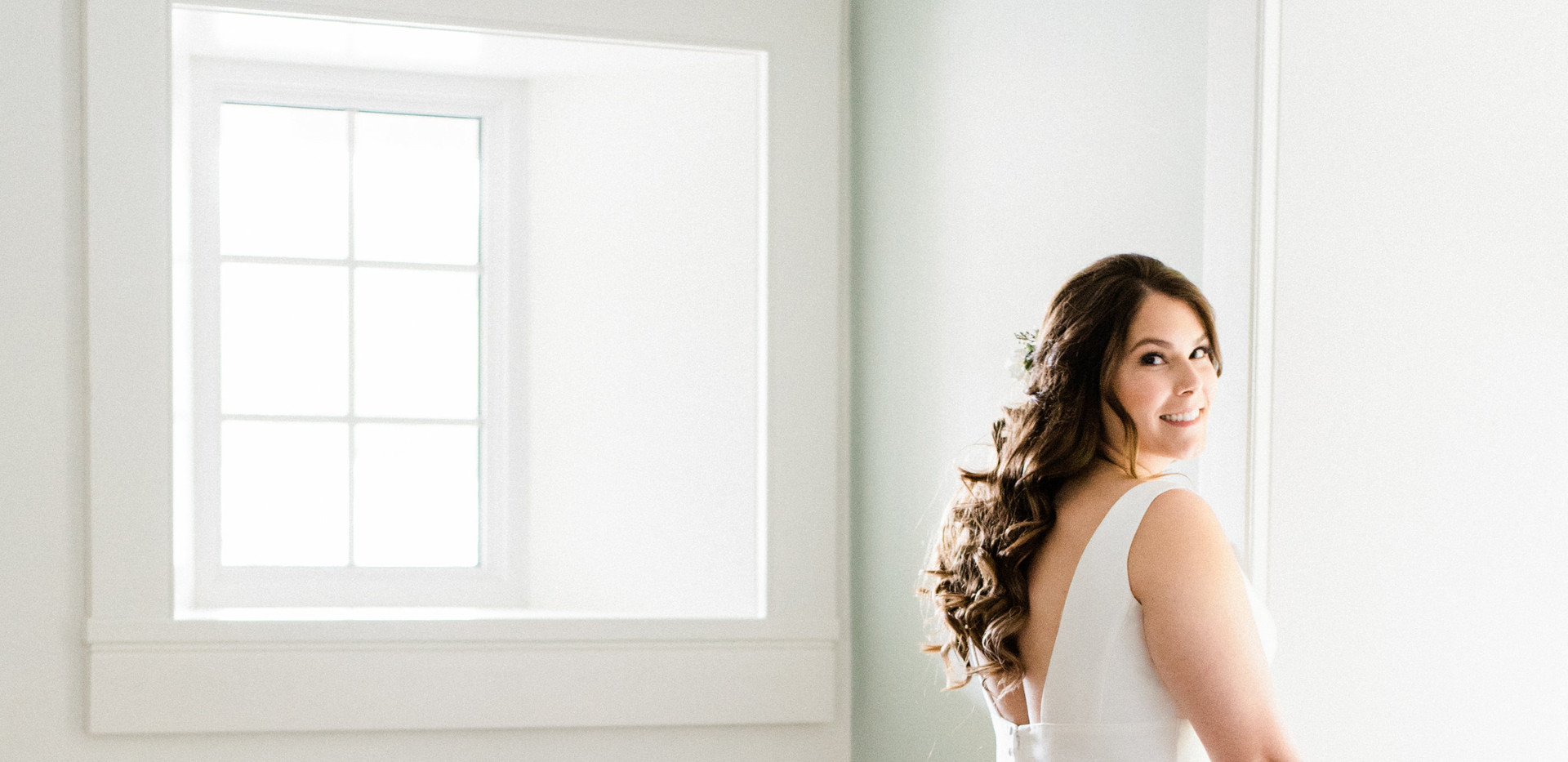 wide shot of bridal looking over her shoulder with her wedding dress train laid out on bridal suite floor