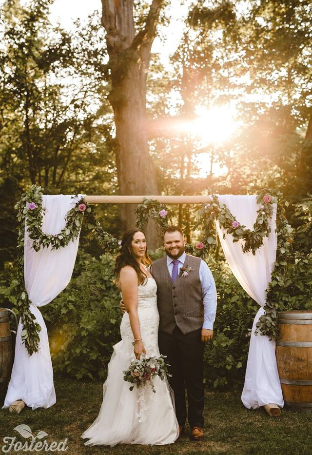 Golden Hour photo of Bride and Groom standing in front of outdoor forest ceremony arch with floral greenery garland