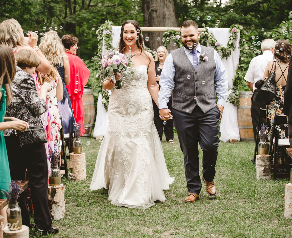 Bride and Groom doing their recessional walk down the aisle while guests blow bubbles at them