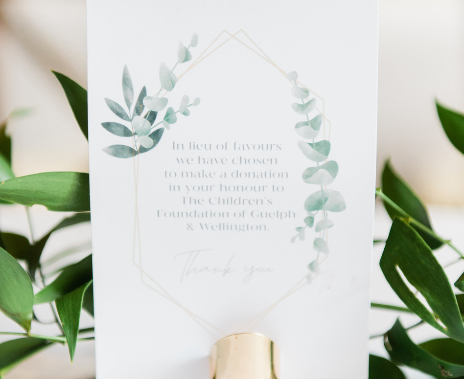 close up of modern greenery themed stationery favours sign with gold sign holder
