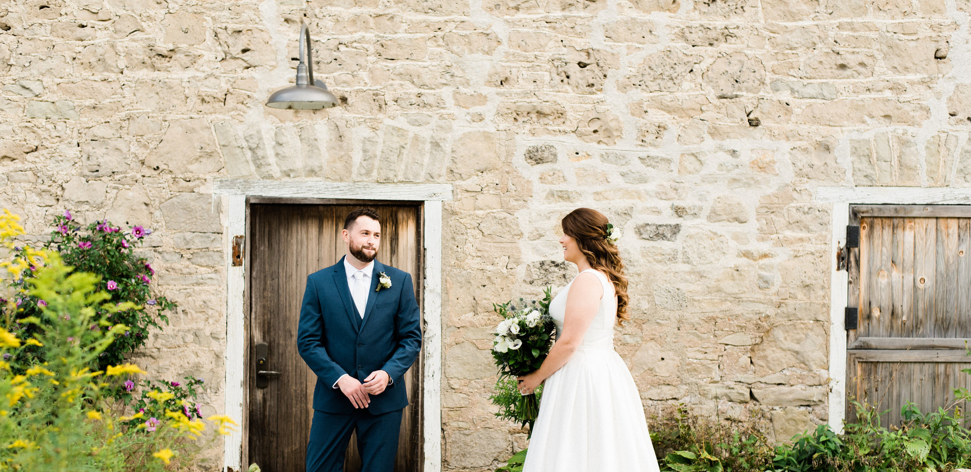 the moment the groom gets his first look at the bride holding her bouquet in her wedding dress next to white stone barn