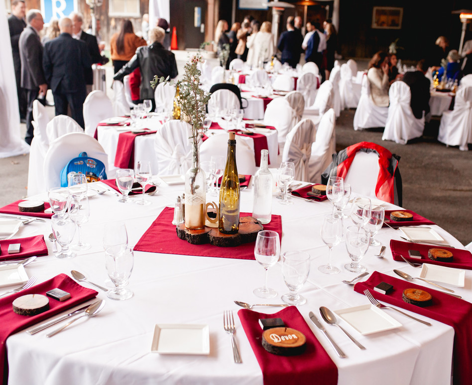 Wide shot of round guest reception table with burgundy napkin, wood slab place cards, and rustic centerpieces
