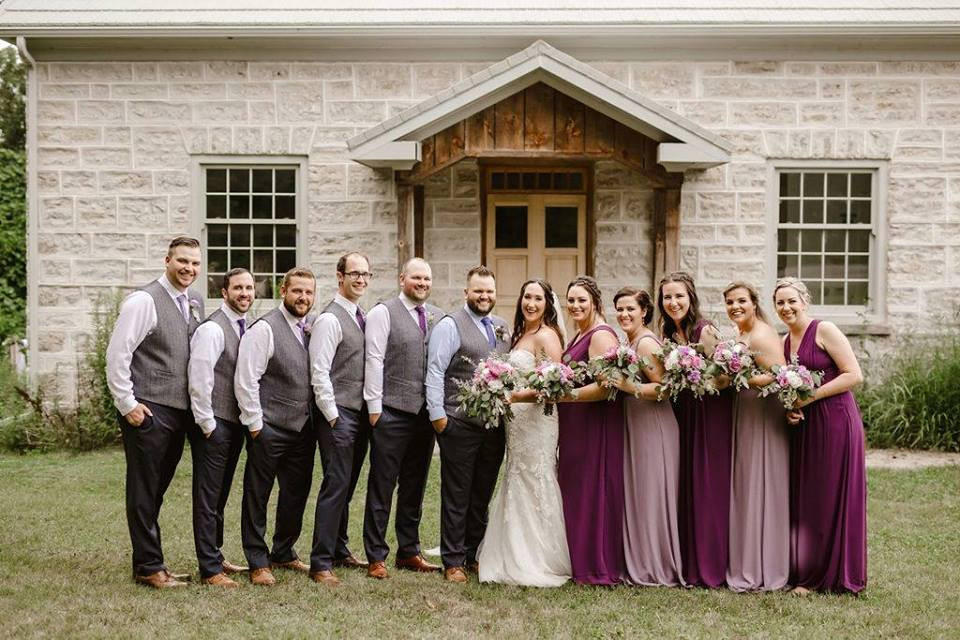 Whole Wedding Party standing side by side in front of farmhouse