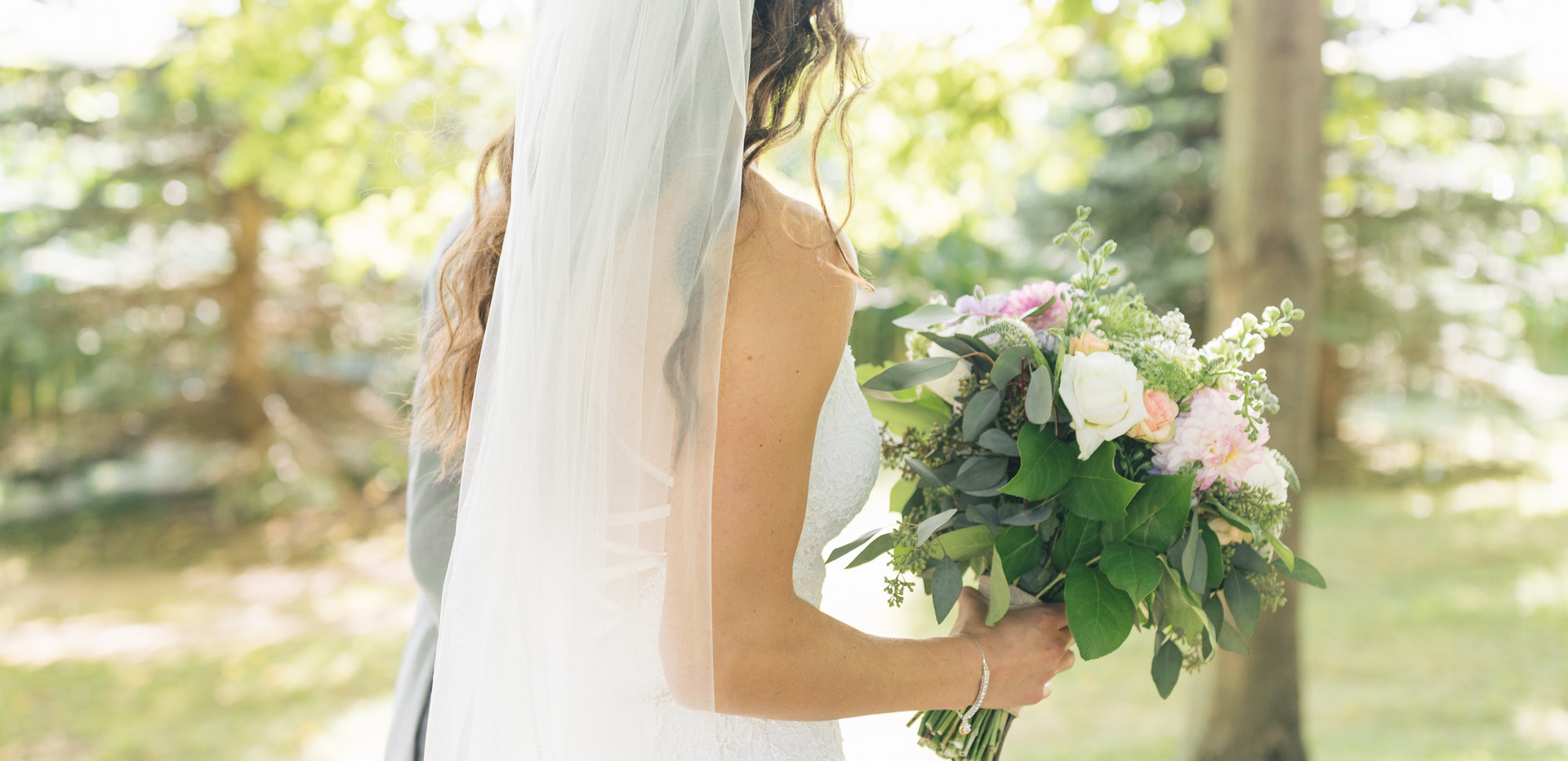 back side view of bride with veil and bouquet