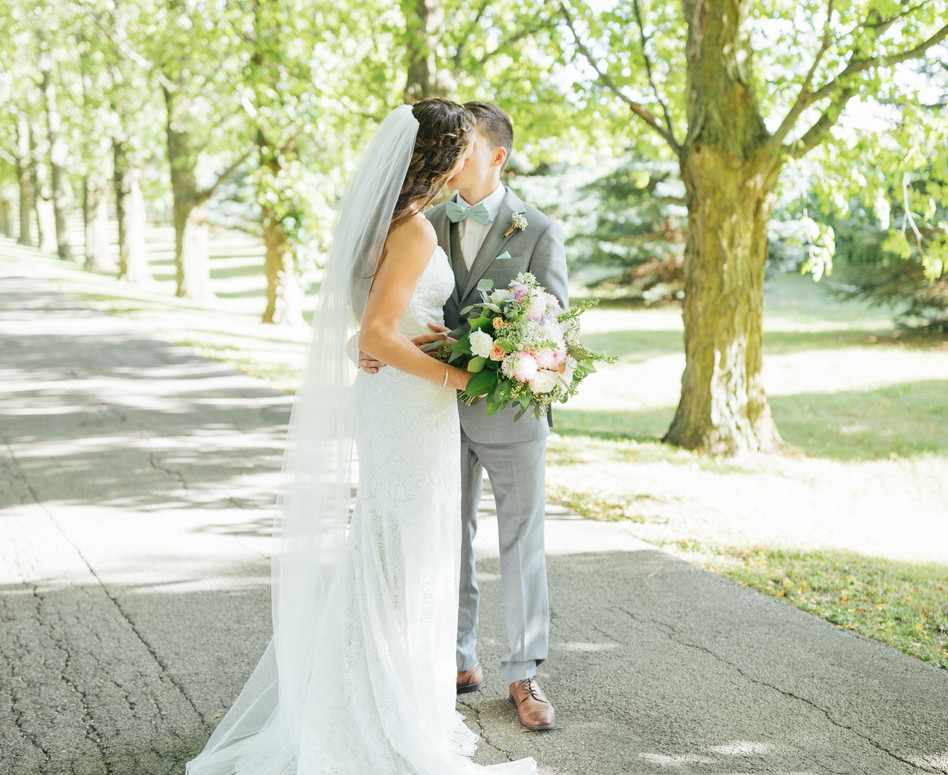 bride and groom kissing on tree lined private laneway