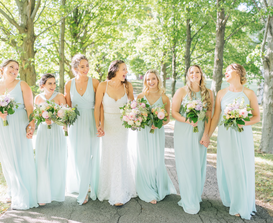 bridal party walking side by side up tree lined laneway
