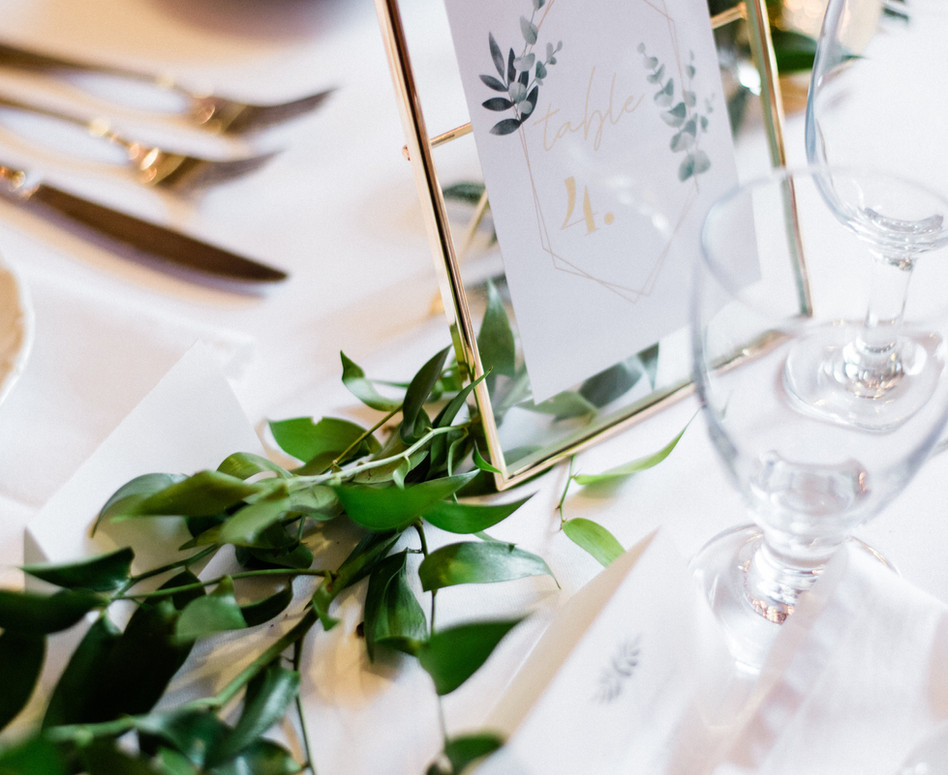 Detail shot of guest table with gold framed geometric table number with loose ruscus greenery runner