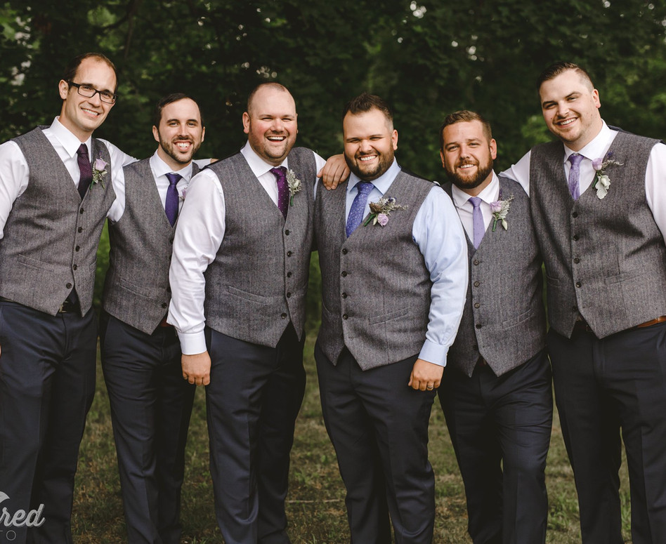 Groom and Groomsmen standing side by side with their grey wedding vests
