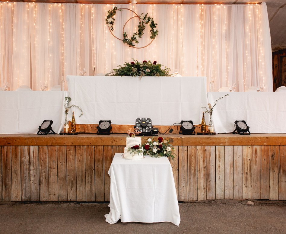 Wide shot of Refined Rustic Glam Head Table on stage with twinkling lights and white sheer backdrop