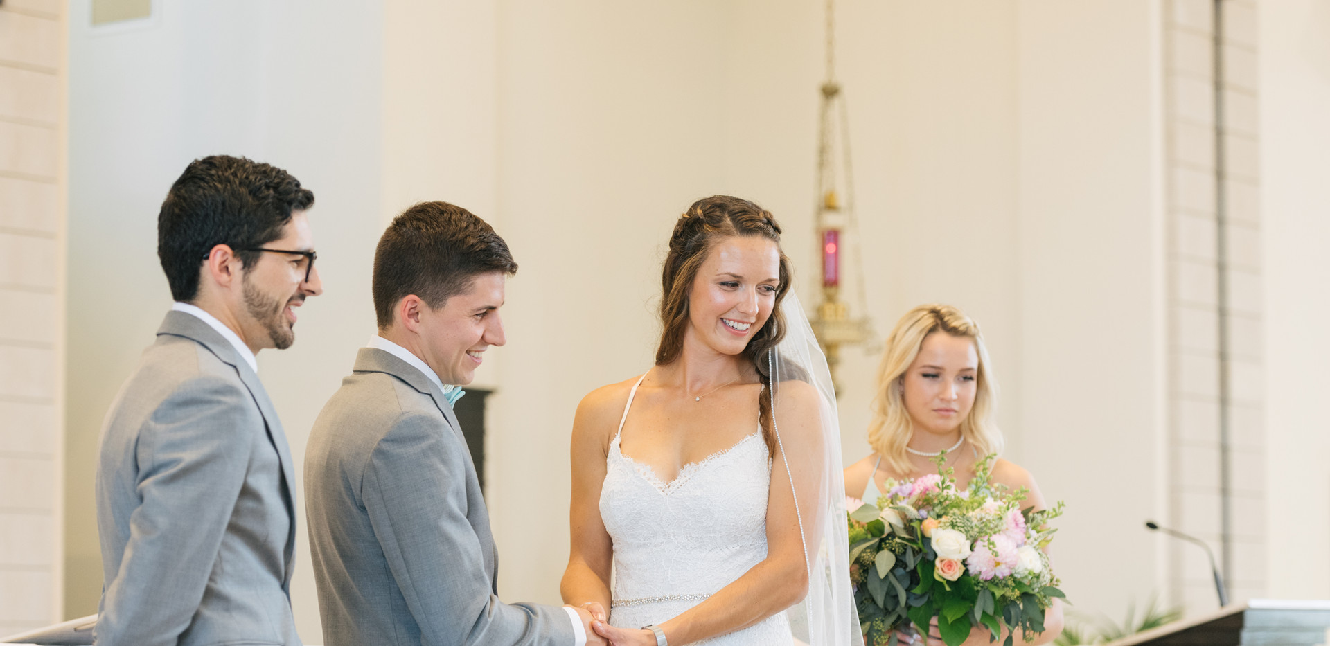 bride and groom standing at altar of church ceremony with best man and maid of honour