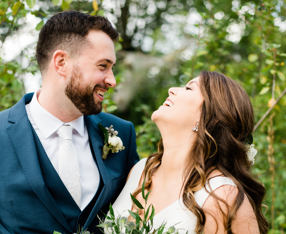 bride and groom gazing in laughter at eachother holding lush white wild greenery bouquet