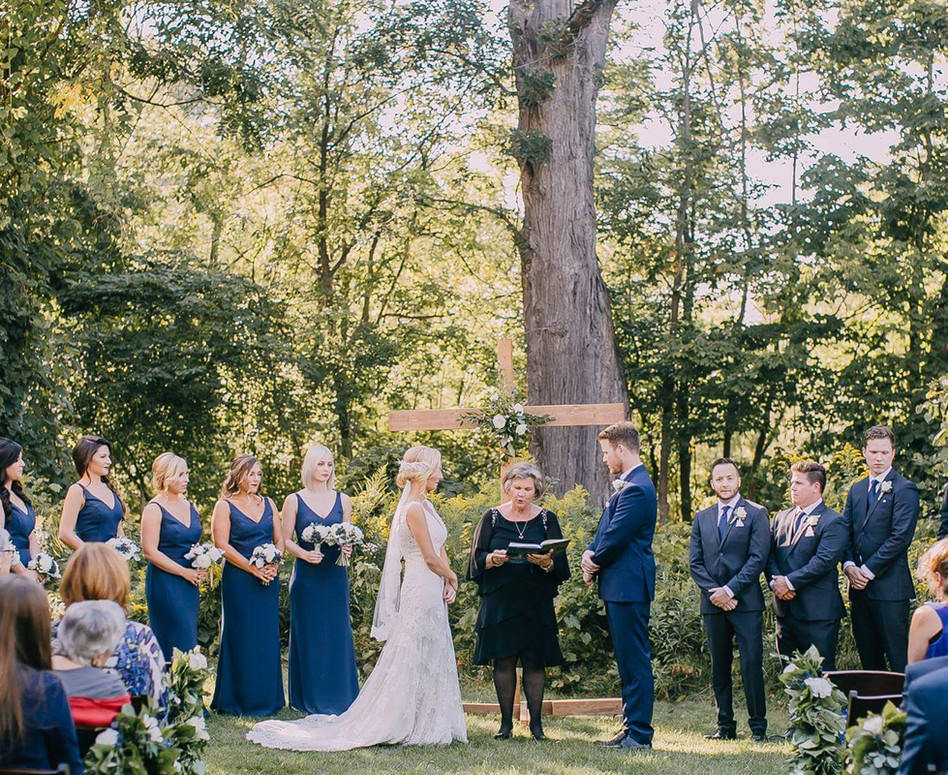 View down Outdoor Ceremony Aisle with Wedding Party standing at Altar