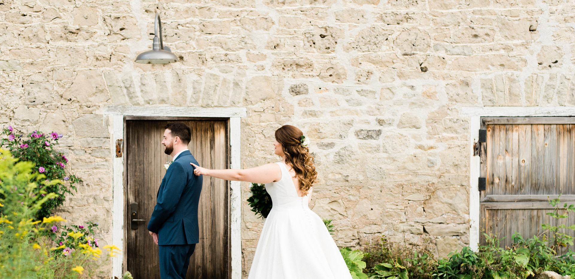 the moment bride taps groom on the shoulder for their first look against white stone barn