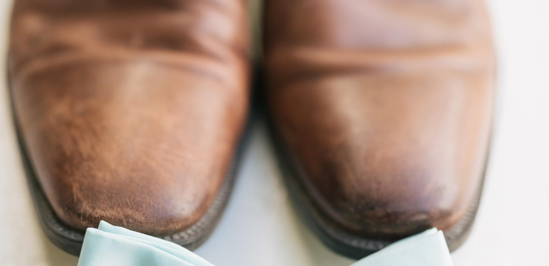 detail shot of grooms shoes, bow tie and wedding band ring