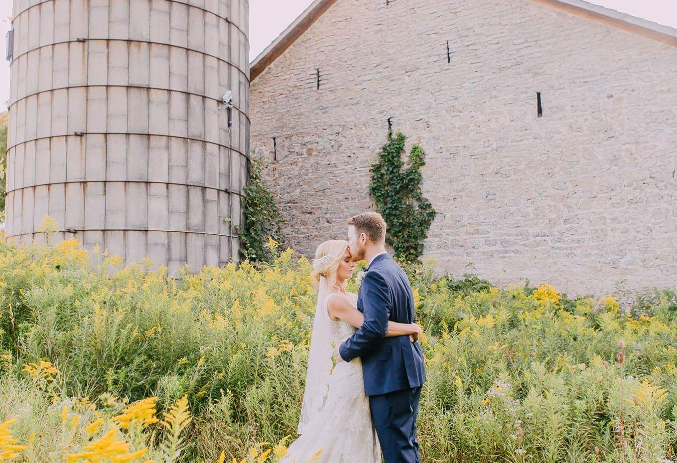 Bride and Groom posing in front of White Stone Barn with Silo, among a field of golden yellow wildflowers