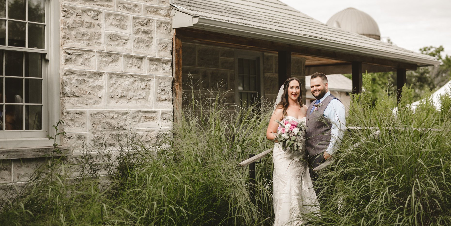 Wide shot of Bride and Groom standing among long grass in front of farmhouse