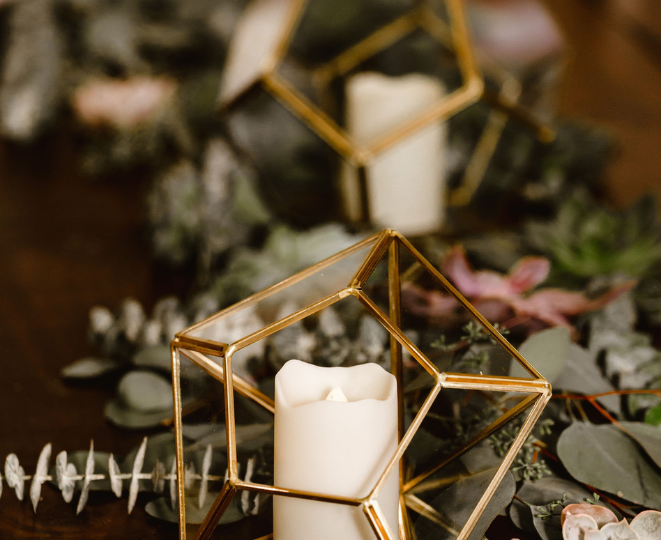 Detail shot of Eucalyptus and Succulent Greenery Table Runner with Gold Geometric candle holders and sprigs of dried lavender