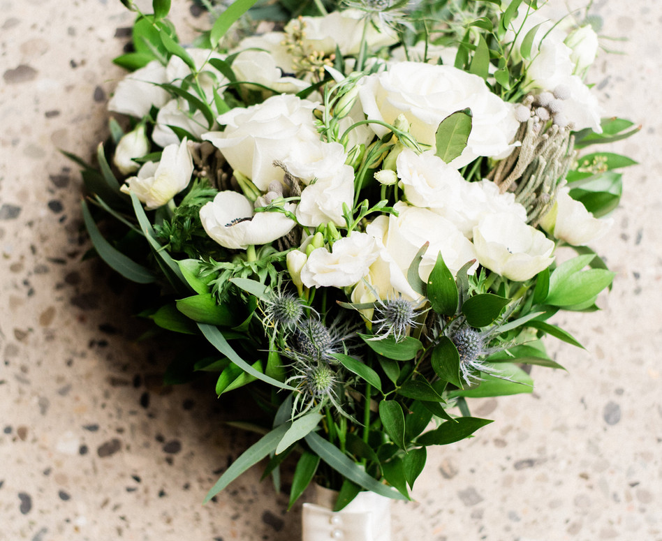 close up shot of lush white wild greenery bridal bouquet laying flat on ground with anemones and blue thistles