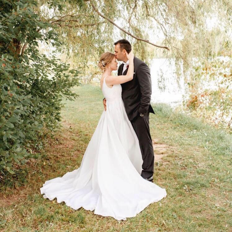 Newlyweds Posing along riverbank with wedding dress train fanned out