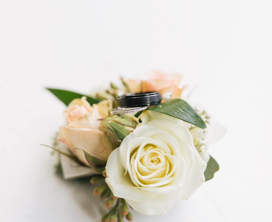simple white and peach rose bouttoniere with groom wedding band ring