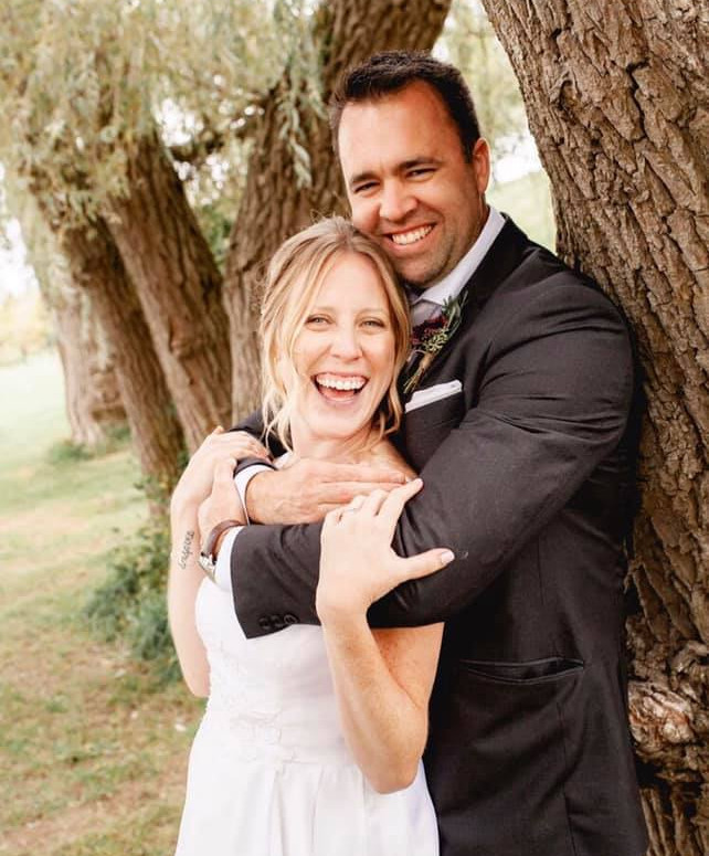Newlyweds Posing next to a Willow Tree, both with the biggest smiles on their faces