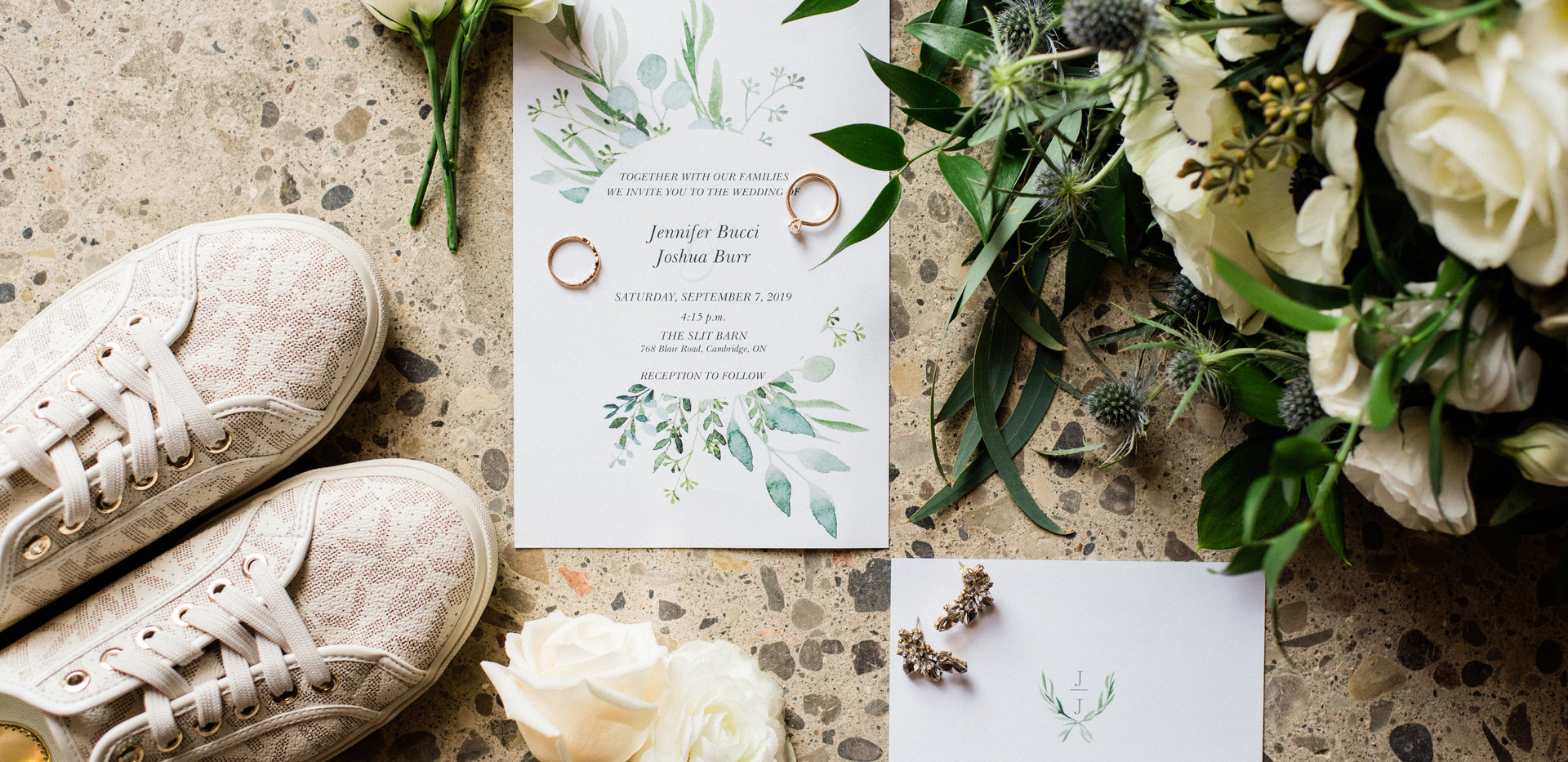 stationery invitation flat lay with bouquet, brand name sneakers, and rings