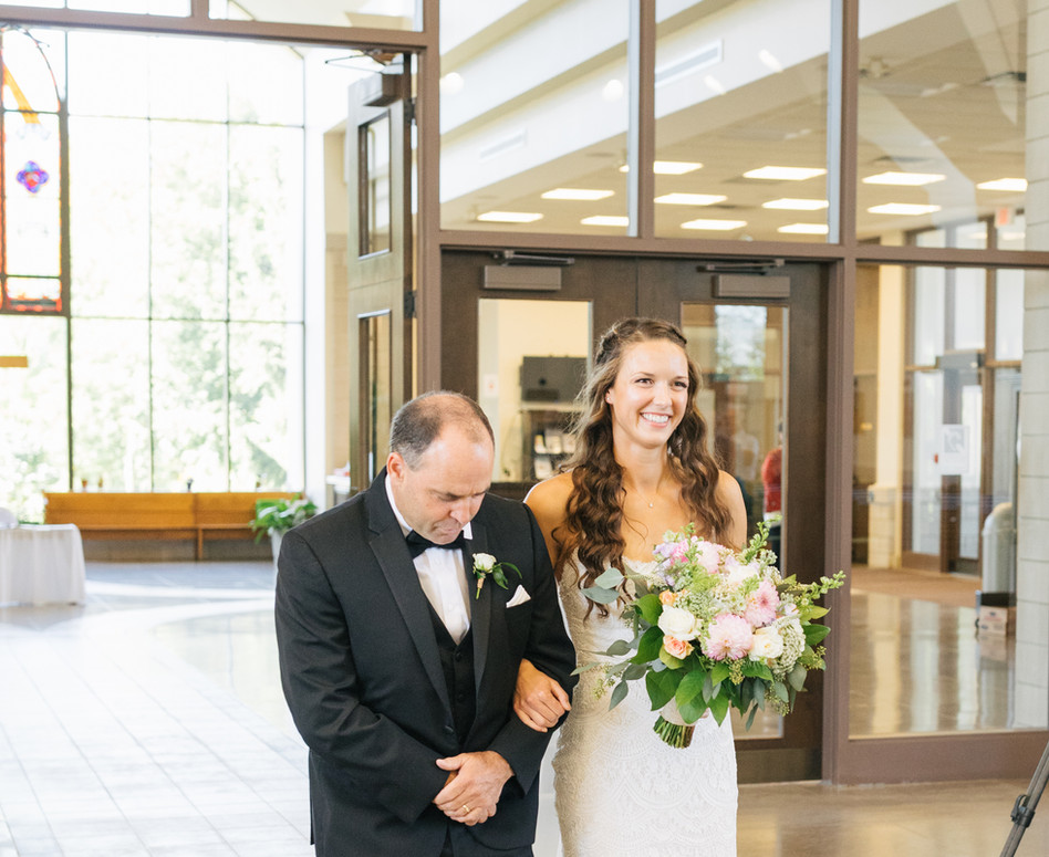 bride being walked down aisle with father in church