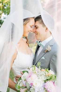Bride and Groom smiling while looking down and have their foreheads touching, pastel blooms bouquet held in front of couple