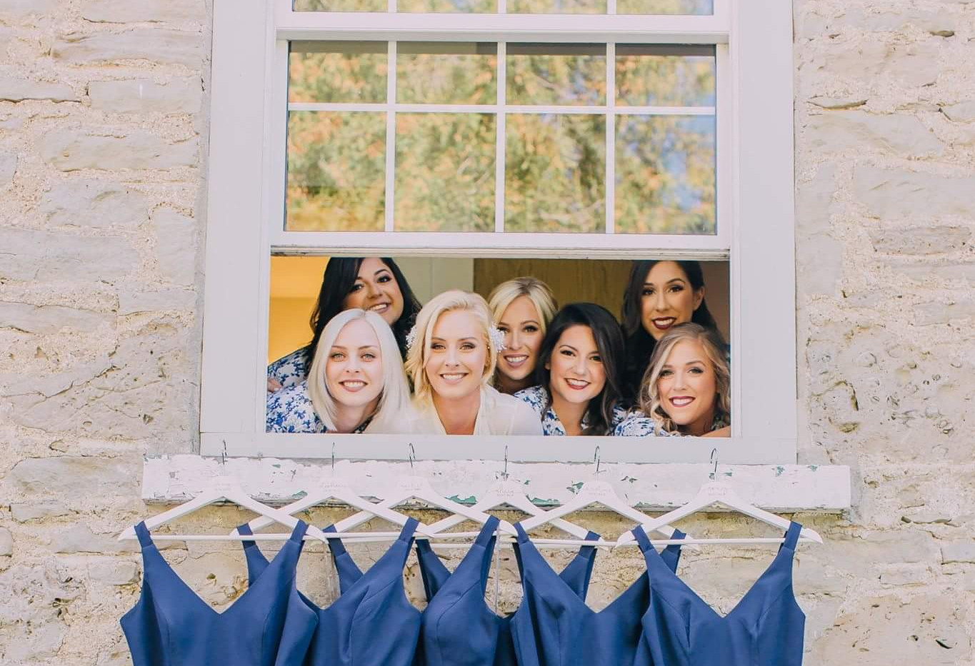 Group photo of bridal party looking out window of farmhouse with their bridesmaid dresses hung below them