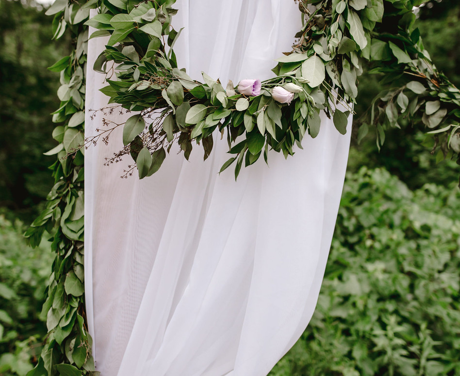 Detail Close up shot of ceremony arch white sheer panel with greenery/floral garland