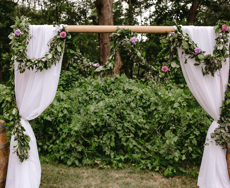 Close up of Outdoor Forest Ceremony Arch with white sheer paneling and greenery/floral garland swagged along wooden arch with wine barrels on either side