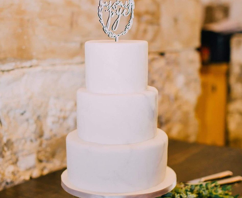 3 Tier Classic White Wedding Cake with Cake Topper and Greenery pieces under the gold stand base