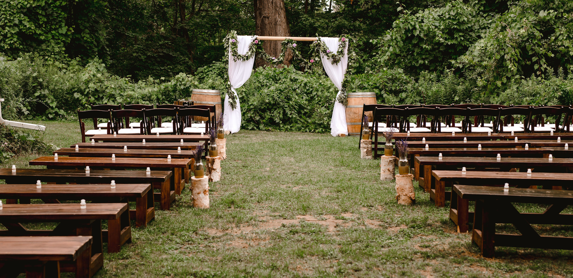 Rustic Forest Ceremony with benches, espresso garden chairs and floral eucalyptus garden arch