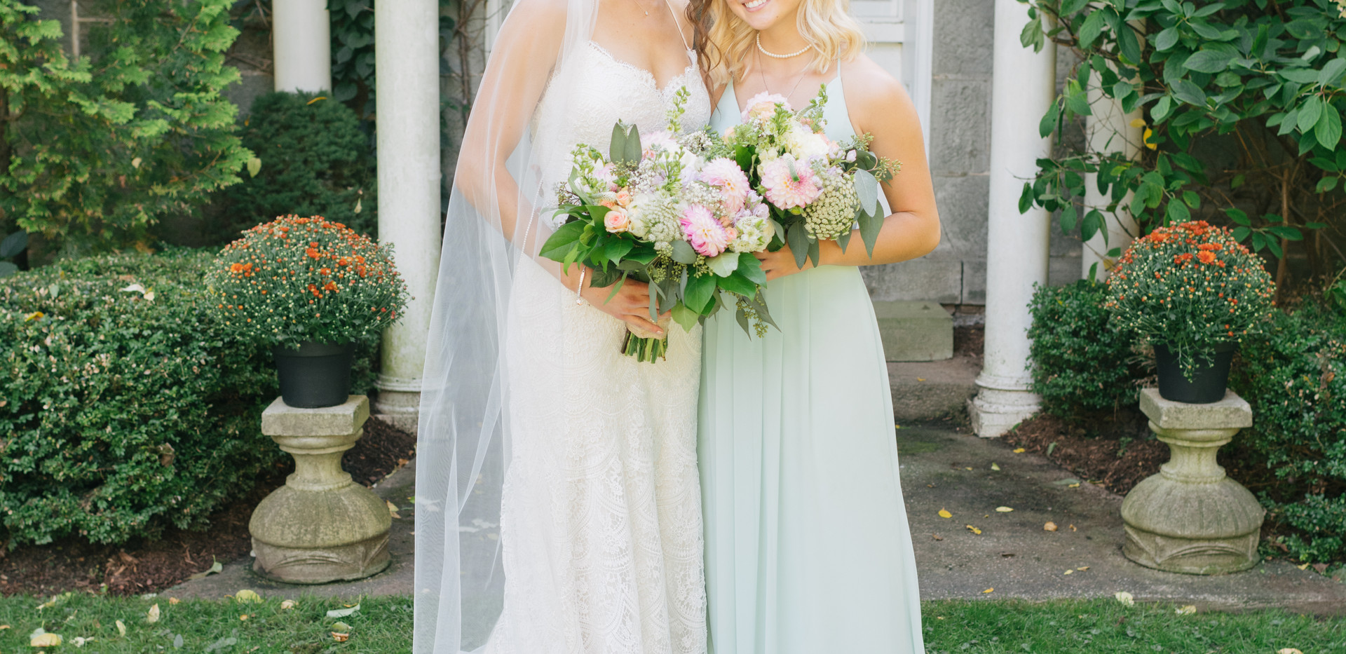 bride and maid of honour with bouquets in front of farm house