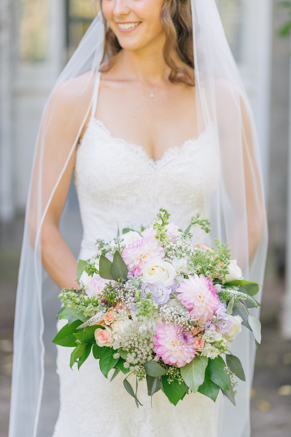 Bride holding her loose styled, pastel coloured bouquet. Full of Dahlias, Spray Roses, Queen's Anne Lace, Veronica, Seeded Eucalyptus, Salal, Babies Breath