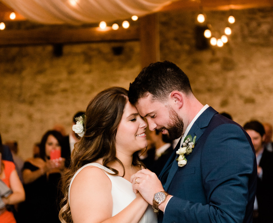 close up of bride and groom during their first dance under white draping and espresso bulb lighting