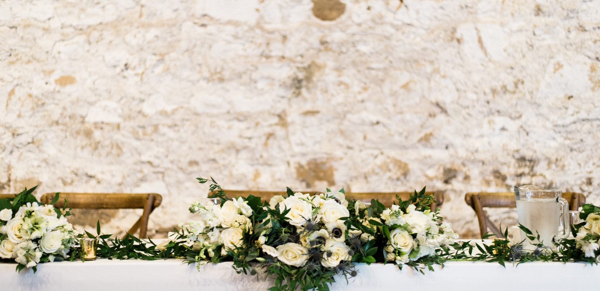 wide shot of white wild greenery bouquets laid flat on head table