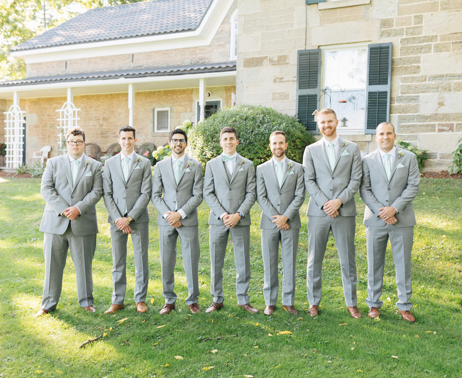 groomsmen standing side by side in front of private farmhouse