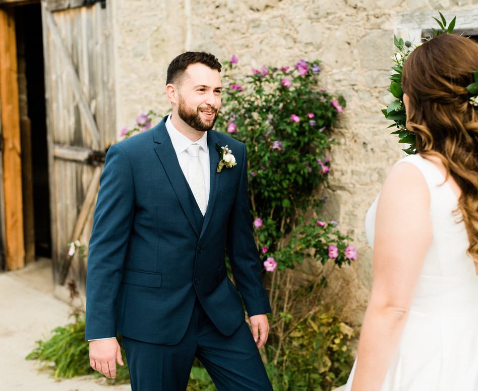 first glances between bride and groom during their first look against white stone barn