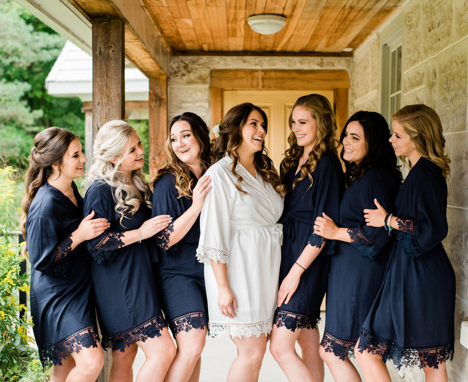 bridal party in navy lace robes standing side by side smiling at eachother on wrap around porch of bridal suite farm house