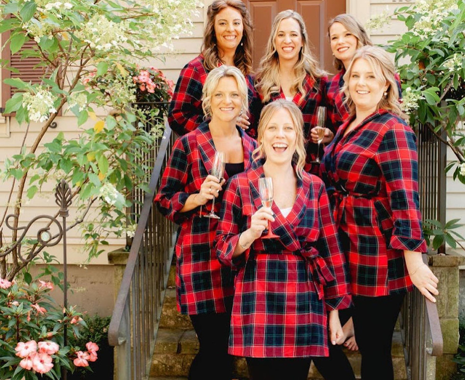 Bridesmaid in red and black plaid robes, sipping champagne on front door steps of their bridal suite house
