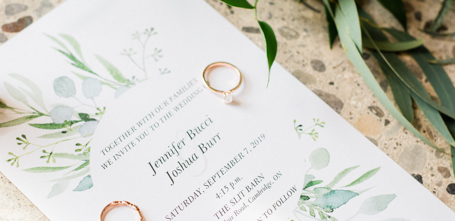 invitation flat lay with wedding rings with bouquet laid beside