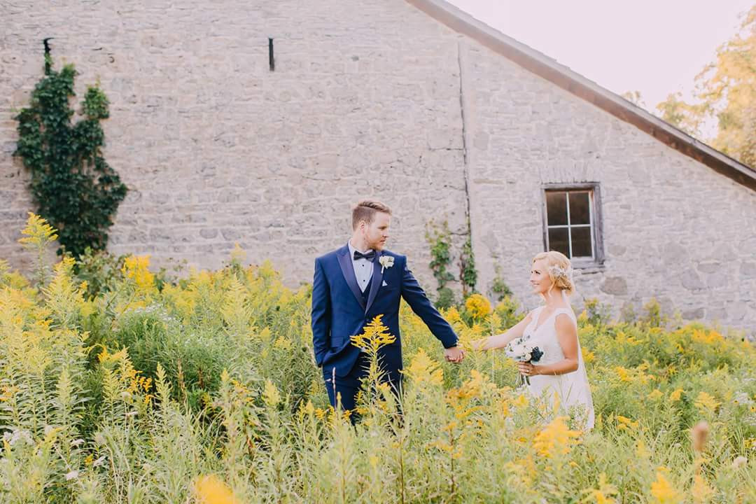 Newlyweds holding hands walking through yellow bloom grass field