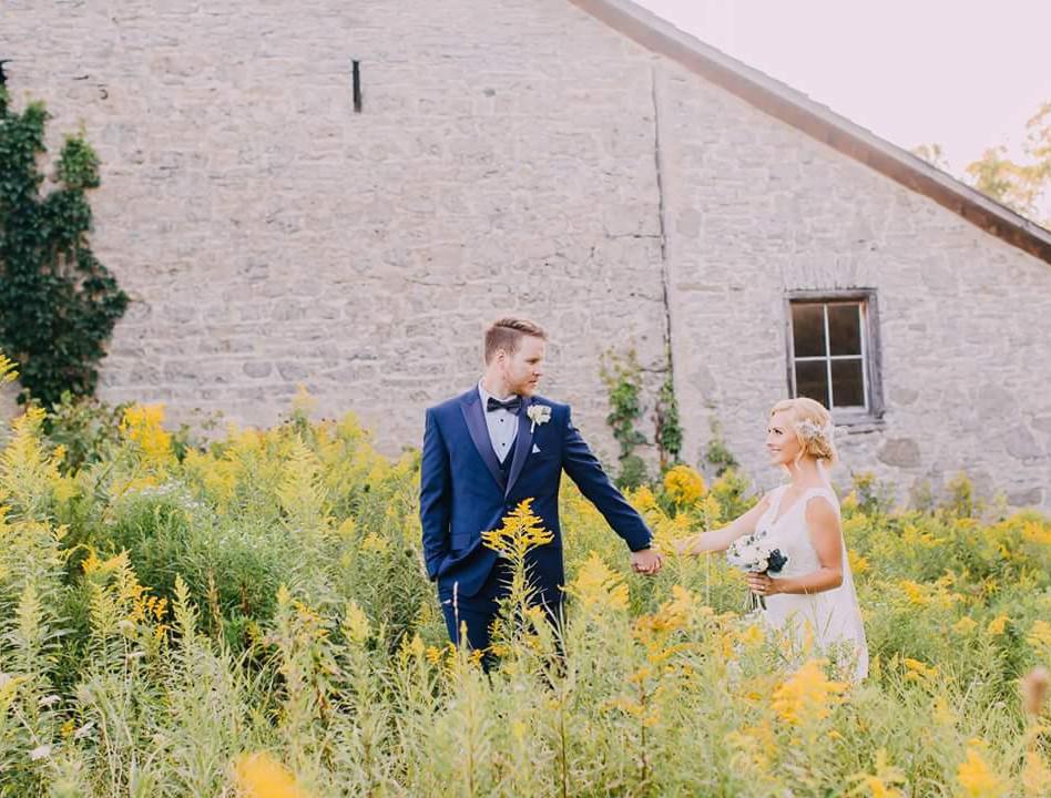 Newlyweds holding hands walking through yellow bloom grass field