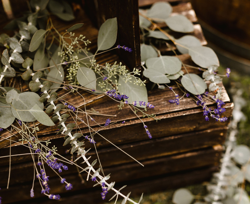 close up shot of decor accessories at ceremony arch, loose varieties of eucalyptus and dried lavender nestled on top of dark stain wood crates and black lanterns
