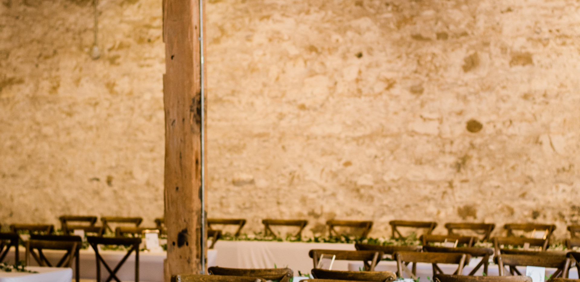 close up shot of white stone barn reception with white ceiling draping and vineyard chairs
